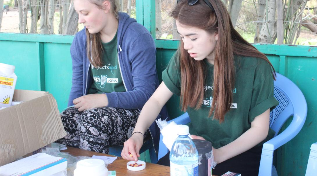 A couple of teenage medical volunteers prepare medicines and equipment for a medical outreach in Kenya while doing their medical internship with Projects Abroad.